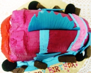 A top view of the cake, the smeecha is swimming on a little blue cream sea surrounded by choclates